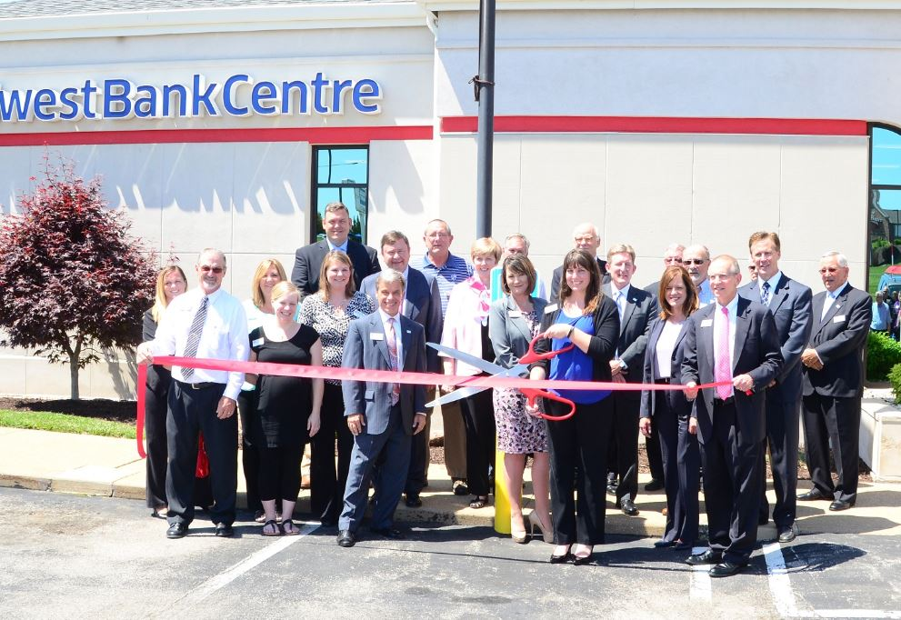 Midwest BankCentre Arnold BankCentre Leader Cristy Heuer (with scissors), flanked by Senior Vice President Suzanne Scherrer (immediately left) and other branch staff, bank leaders and bank board members prepare to cut the ribbon celebrating the grand re-opening of the bank's newly remodeled Arnold branch on June 10. The bank is celebrating its 25th anniversary of serving the Arnold community.